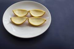 桔子削减了对在被吃的白色板材的切片 果皮 免版税库存图片