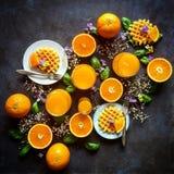 桔子和奶蛋烘饼花卉早餐 库存照片