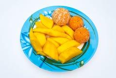 桔子和成熟芒果许多片断板材没有果皮的, 免版税库存图片