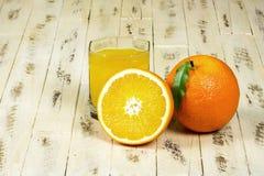 桔子和杯木表面上的橙汁 图库摄影