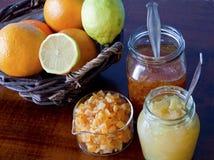 桔子和柠檬篮子,两被打开的果酱瓶子和糖煮 免版税库存照片