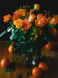 桔子和橙色玫瑰在木桌上 免版税库存图片