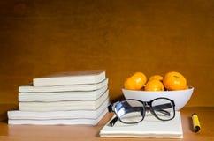 桔子和玻璃在笔记本和书在木桌上 库存照片