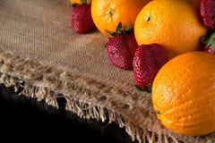 桔子和草莓在黑色制表果子背景 免版税库存照片