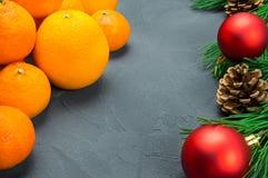 桔子和蜜桔与分支圣诞树和红色球在黑具体背景 免版税图库摄影