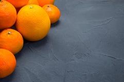桔子和蜜桔在葡萄酒黑色混凝土背景 免版税库存照片