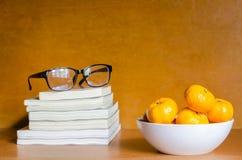 桔子和玻璃在书在木桌上 免版税库存照片
