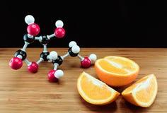 桔子和维生素C结构模型(抗坏血酸) 免版税库存图片