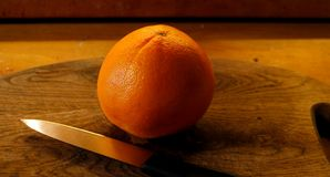 桔子在一木choppingboard说谎在一把小果实刀子旁边 免版税库存图片