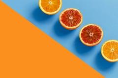 桔子在橙色和蓝色背景切成了两半 图库摄影