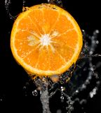 桔子在黑背景的水中 免版税库存图片
