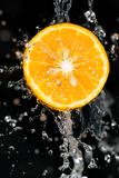 桔子在黑背景的水中 库存照片
