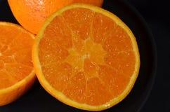 桔子在黑色的盘子切成了两半 免版税库存照片