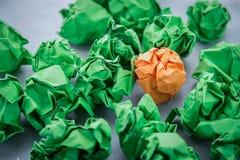 桔子弄皱了在绿色被弄皱的纸创造性co之间的纸 库存图片