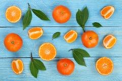 桔子或蜜桔与叶子在蓝色木背景 平的位置,顶视图 果子构成 免版税库存图片