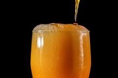 桔子汽水大玻璃,溢出的杯与在黑色隔绝的泡影的桔子汽水特写镜头 免版税库存照片