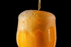 桔子汽水大玻璃,溢出的杯与在黑色隔绝的泡影的桔子汽水特写镜头 库存照片