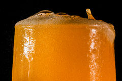 桔子汽水大玻璃,溢出的杯与在黑色隔绝的泡影的桔子汽水特写镜头 图库摄影