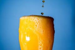 桔子汽水大玻璃,溢出的杯与泡影的桔子汽水特写镜头在蓝色 免版税库存图片