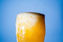 桔子汽水大玻璃,溢出的杯与泡影的桔子汽水特写镜头在蓝色 库存图片