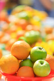 桔子用在色的背景的苹果 免版税库存图片