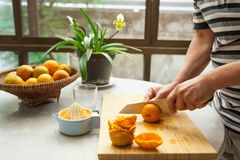 桔子用手被紧压做纯净和健康橙汁 库存图片