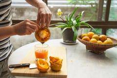 桔子用手被紧压做纯净和健康橙汁 库存照片