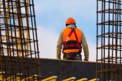 桔子的工作者与在建造场所的安全带 免版税库存图片