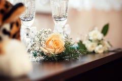 从桔子的钮扣眼上插的花在木桌上上升了 免版税库存照片