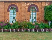 桔黄色有用绿色金属栅格、绿草地板和灌木盖的两个大老难看的东西窗口的砖石墙 库存图片