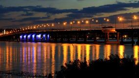 桥梁在晚上,光在水反射了 库存照片