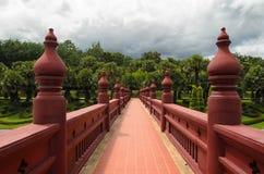 桥梁在红色导致paited有棕榈树的一个绿色公园 免版税图库摄影