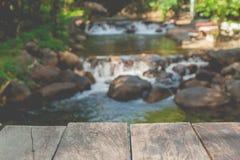 桥梁木地板有小瀑布美好的风景视图在有流经石头的水小河的河 库存照片