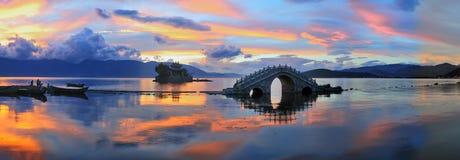 桥梁湖小的日落寺庙 库存图片