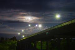 桥梁点燃了与月亮和灯通过河在夜城市 免版税库存照片