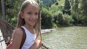 桥梁的孩子在山,孩子步行本质上的,看河,小河的女孩 股票视频