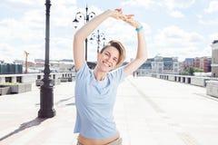 桥梁的年轻微笑的妇女在都市风景背景  免版税库存照片