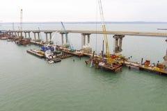 桥梁的建筑 一座铁路和汽车桥梁的建筑的工程学设施横跨海峡的 免版税库存图片