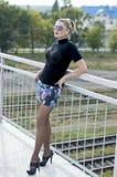 桥梁的性感的美丽的妇女在一件超短裙,反对r 库存照片