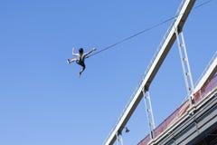 从桥梁的飞跃有绳索的 极端体育,跳跃,肾上腺素 人从有绳索的桥梁跳 免版税图库摄影
