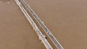 桥梁鸟瞰图横跨建设中泥泞的河的,当交通通过在一条车道 股票视频