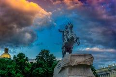 桥梁okhtinsky彼得斯堡俄国圣徒 在日落的古铜色御马者纪念碑 免版税库存照片
