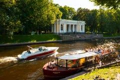 桥梁okhtinsky彼得斯堡俄国圣徒 Rossi亭子在迈克尔庭院和Moika河里有游船的 免版税库存图片