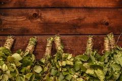 浴桦树和橡木分支的新的笤帚在黑褐色木背景 免版税图库摄影