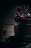 桶、蒸馏瓶和玻璃用红葡萄酒在一个黑暗的地窖里 库存照片