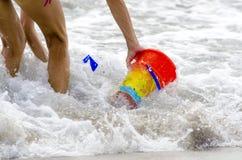 桶和戏剧婴孩的由海洗涤了有胳膊和腿的 库存照片