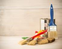绘桶和油漆刷在木头 免版税库存照片