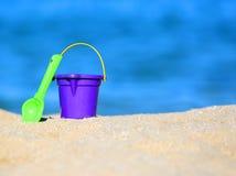 桶和铁锹在沙子在海滨 免版税库存图片