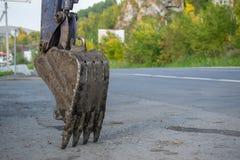 桶挖掘机在路附近 免版税库存图片