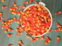 桶糖果玉米在木地板上说出 库存图片